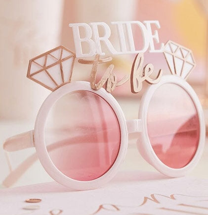 These plastic pink and rose gold sunnies say Bride to Be accented with diamond rings around the rims of the glasses. Get a pair for the Bride to wear at her Bachelorette party or Bridal Shower. She'll be sure to stand out with these rose tinted glasses!