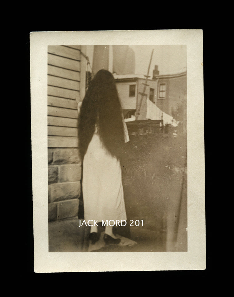 creepy unusual old snapshot photo long black hair girl facing away from camera