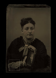 Woman in Mourning Holding Memorial Photo