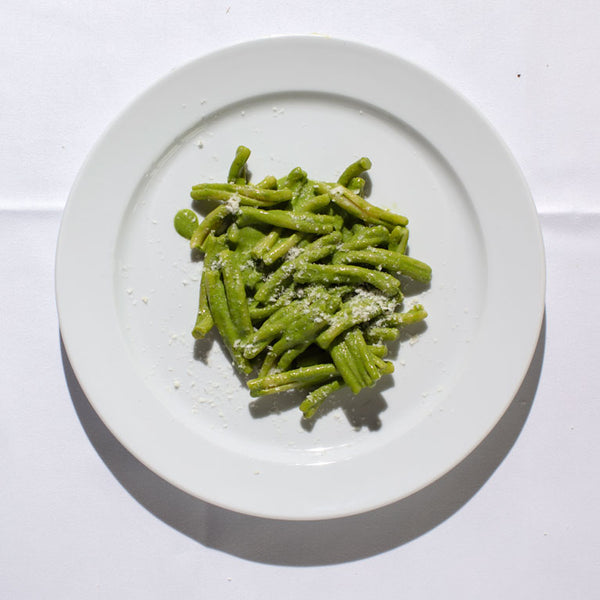 Casarecce pasta coated in bright green pesto with a sprinkling of parmesan.