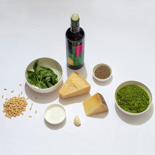 A bowl of basil leaves, a bowl of ground black pepper, a bowl of sea salt, a clove of garlic, some pine nuts, a wedge of parmesan, a wedge of pecorino, a bottle of River Cafe olive oil and a bowl of bright green pesto.