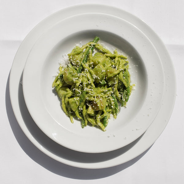 Trofie pasta coated in bright green pesto with a sprinkling of parmesan.