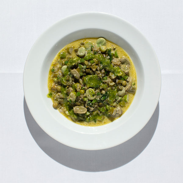 Bright green minestrone of peas, broad beans, green beans and zucchini with pesto swirled on top.