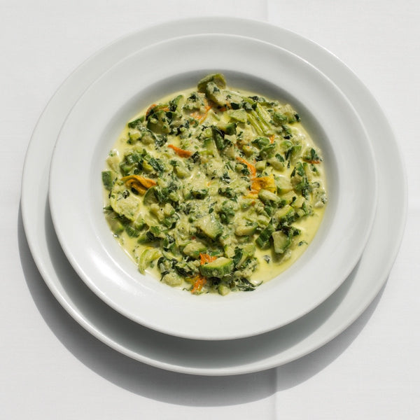 A creamy green soup made with green zucchini and orange zucchini flowers.
