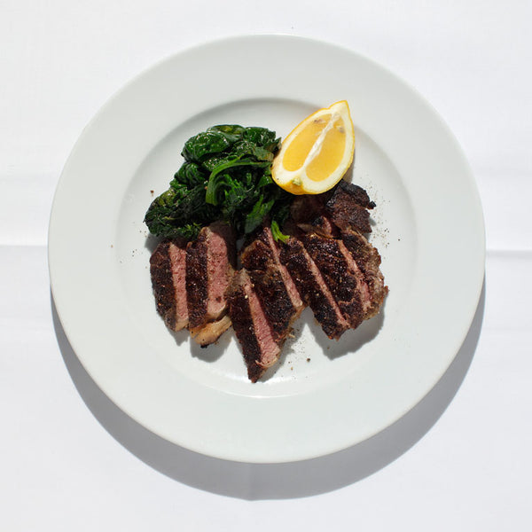 Sliced sirloin steak with a lemon wedge and braised spinach.