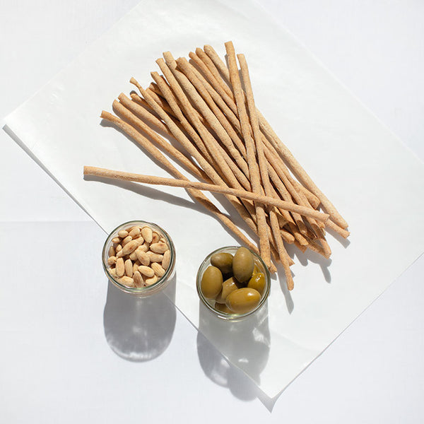 Grissini (breadsticks) and a glass bowl of green olives and a glass bowl of almonds.