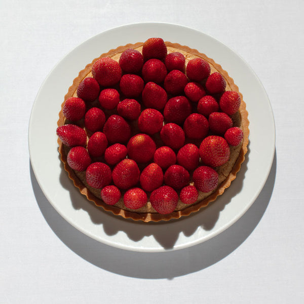 Frangipane almond tart topped with strawberries served on a white plate.