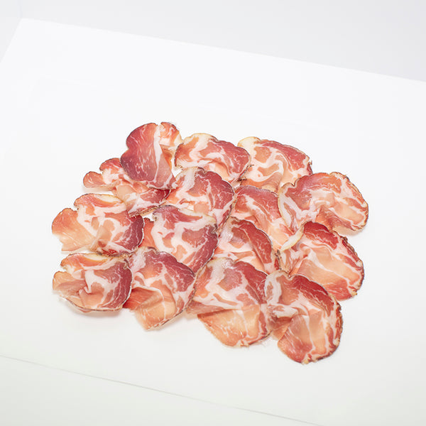 Thinly sliced Coppa di Parma on wax paper.