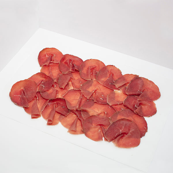 Thinly sliced Bresaola on wax paper.