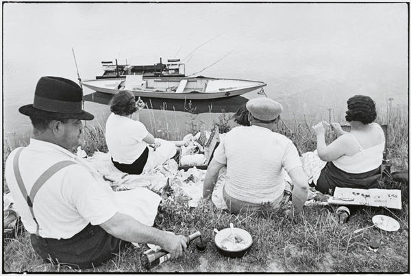 Henri Cartier-Bresson, Picnic on the Banks of the Marne, 1938. Black and white image of four people enjoying a picnic on the banks of the river Marne, France.