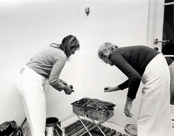 Black and white image of Ruthie Rogers and Rose Gray, founders of the River Cafe, cooking outside on a metal grill