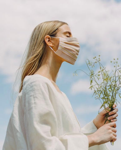 blonde girl with a white shirt wearing a mask and holding flowers outdoors