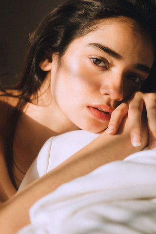 girl with dark eyes and hair with her hands on the bedsheet