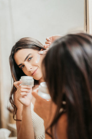 rosafa model putting on a moisturizer on her cheek in the mirror