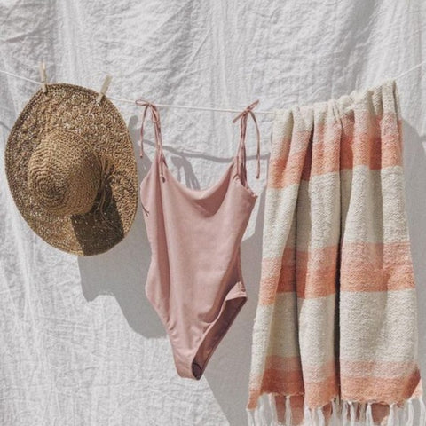 straw-hat-bathing-suit-and-a-towel-hanging-on-a-drying-wire