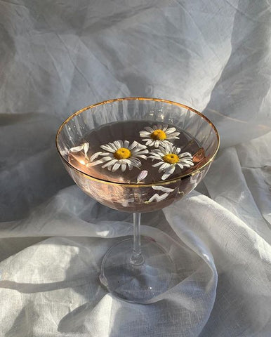tree chamomile flowers floating in a wine glass