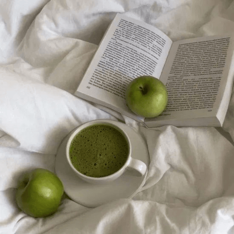 two green apples, green coffee, and a book on the bed