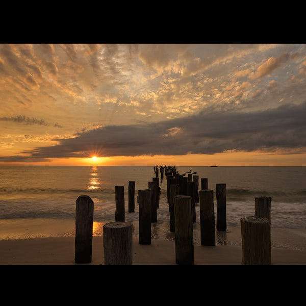 The old pier pilings at Naples Beach at sunset.