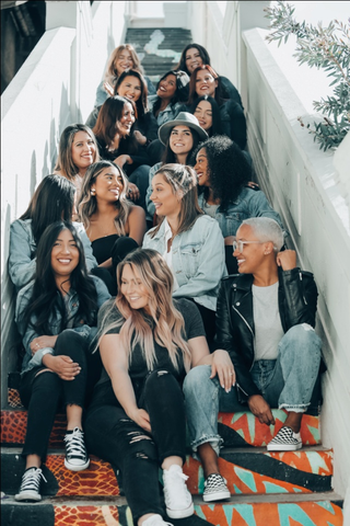 A diverse group of women sitting on stairs