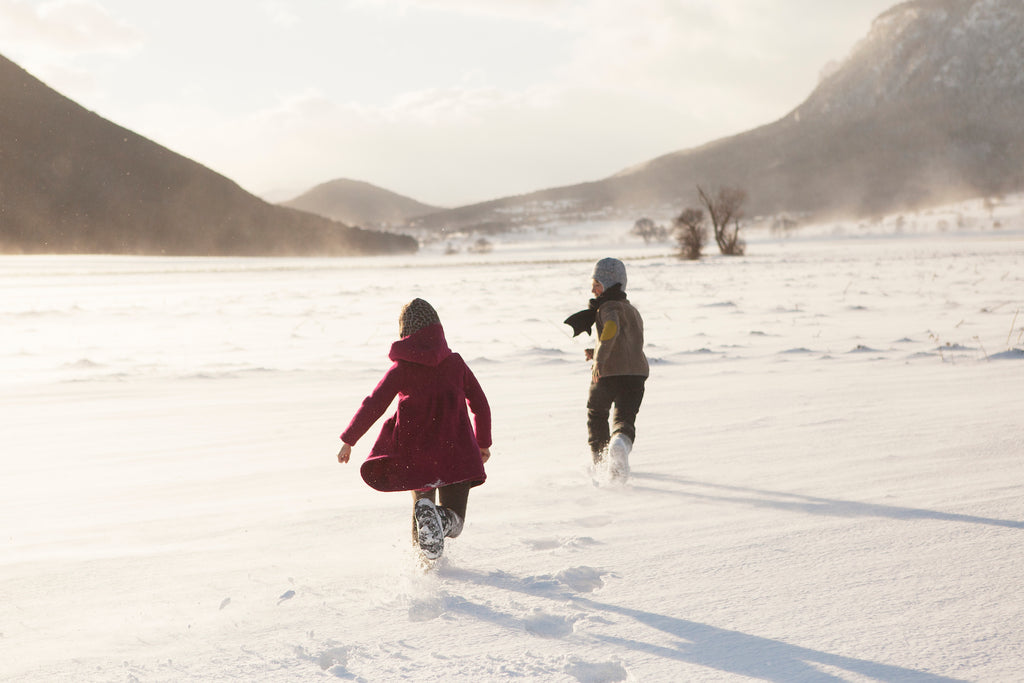 Boy and girl running through wintery Alpine landscape. Both wearing Hilda.Henri coats, jackets, pants and accessories from the Austrian label. High-quality and durable kids clothes. Slow fashion for kids