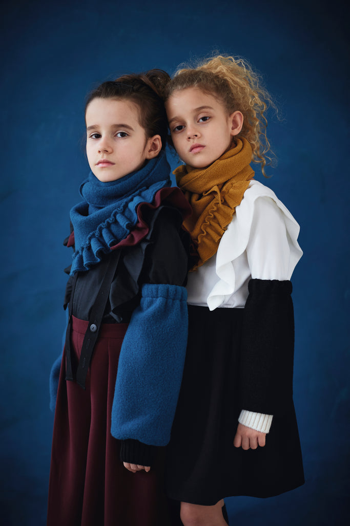 Two girls wearing Hilda.Henri outfits for winter. Skirt, pants blouses and accessories are completing these outfits of extraordinary kids`designer clothing