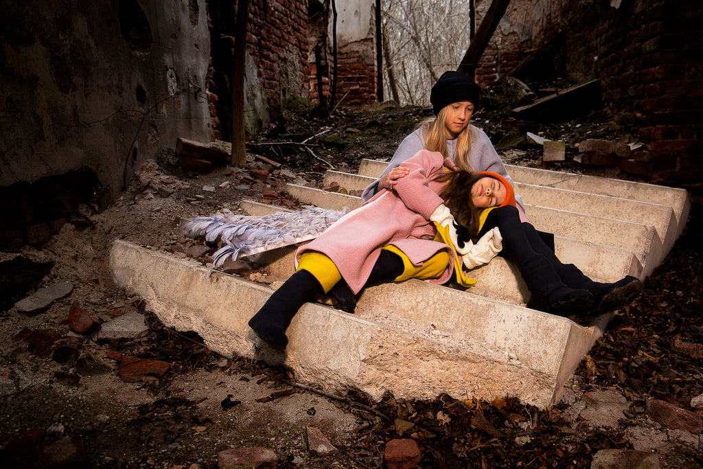 Two girls resting on a broken stairway in a ruin, both wearing sustainable wool clothes from Hilda.Henri