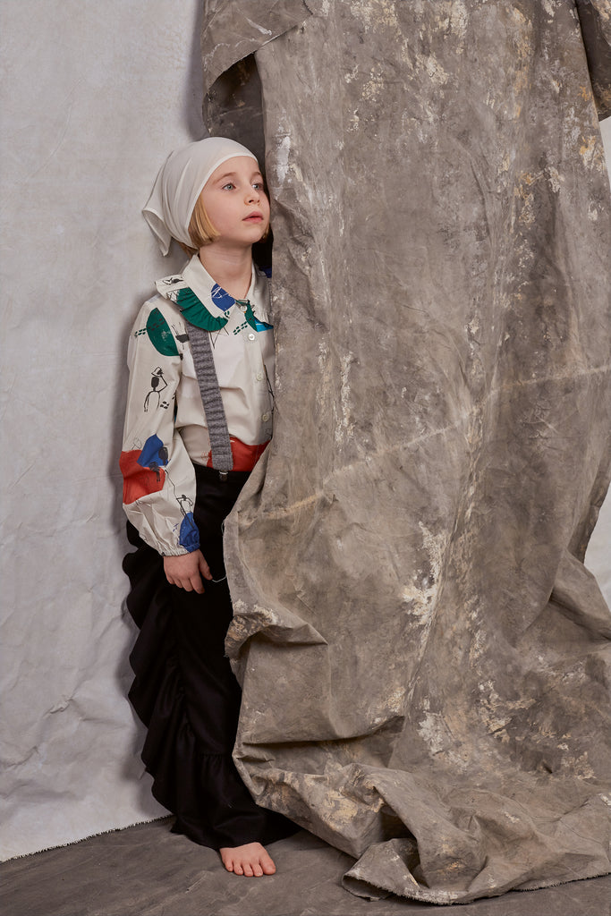 Girl hiding behind decoration wearing Hilda.Henri blouse, pants and suspenders
