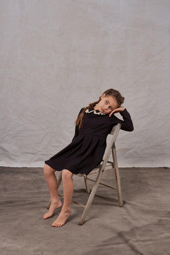 black wool dress with white ruffle detail - worn by a girl sitting on a chair
