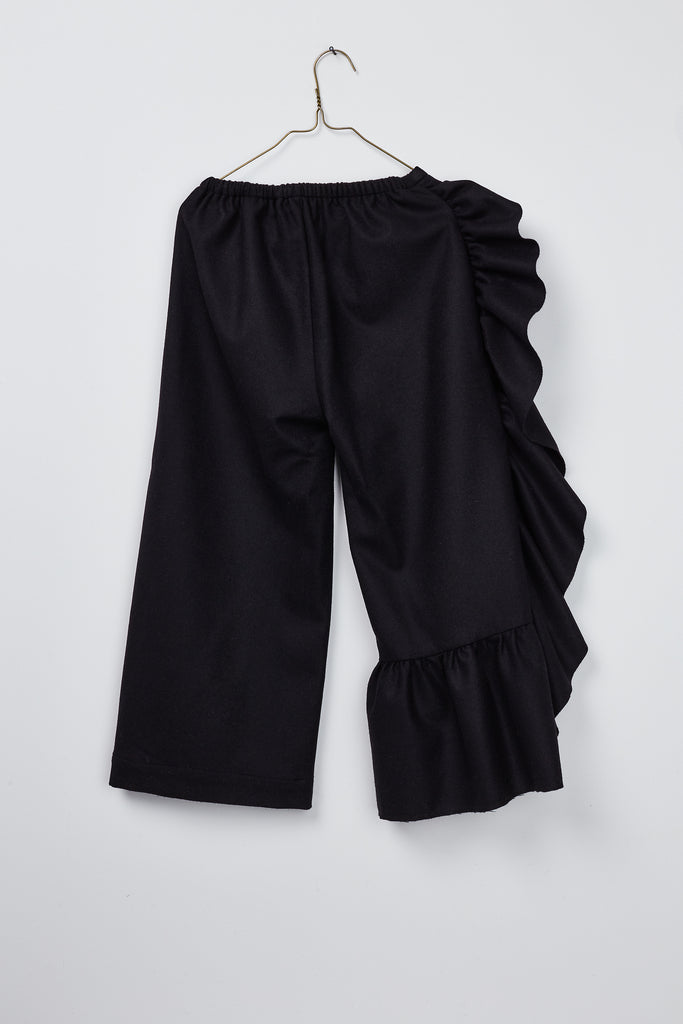 girl`s black wool pant with asymetric ruffle by Hilda.Henri - seen from the rear