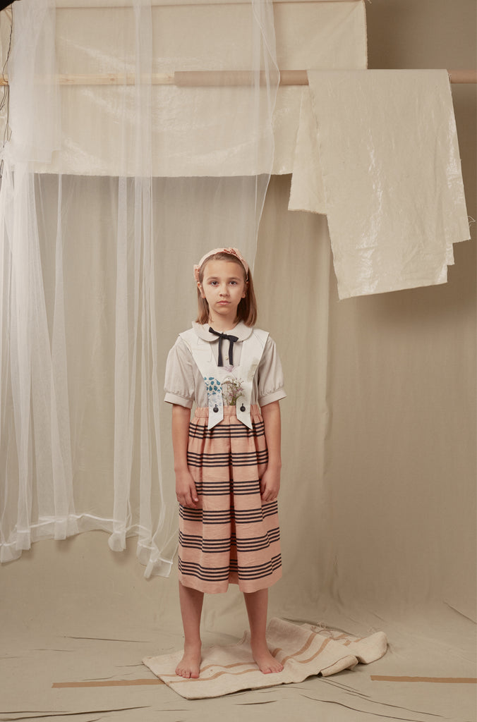 Girl wearing summer outfit by Hilda.Henri with striped midi skirt, collar blouse and matching suspenders with love to detail