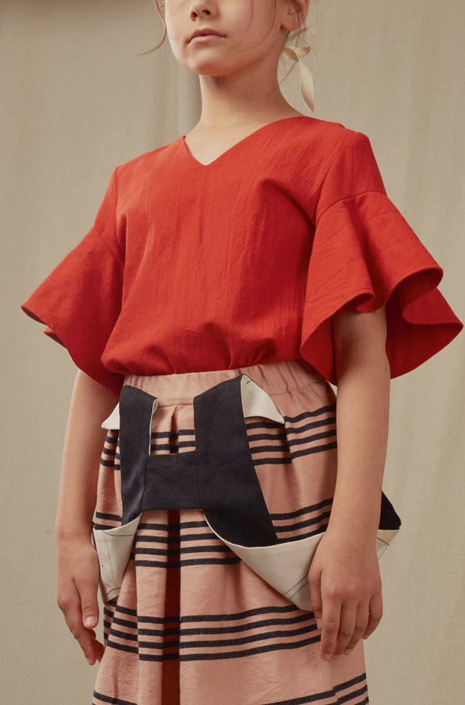 Salmon skirt with stripes, red blouse and reversible suspenders. Hilda.Henri styles for summer