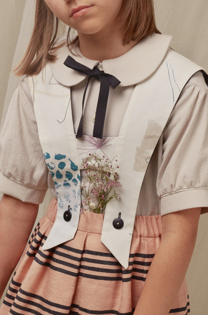 detail of printed suspenders, cotton blouse with bow and striped skirt. girl`s outfit by Hilda.Henri