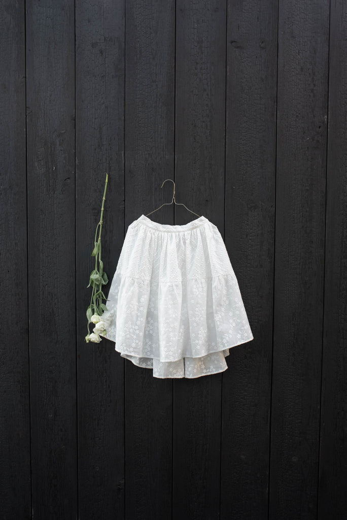 white Hilda.Henri skirt with embroidery on hangar in front of dark background