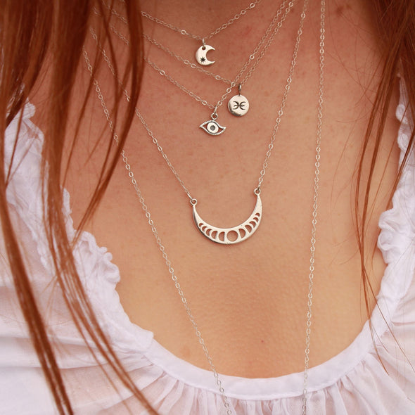 Sterling Silver Zodiac Leo necklace layered with other necklaces on model.