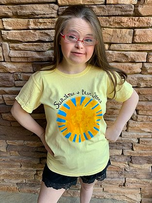 Young woman wearing yellow t shirt with golden sun with blue rays beneath Sunshine and Blue Skies slogan
