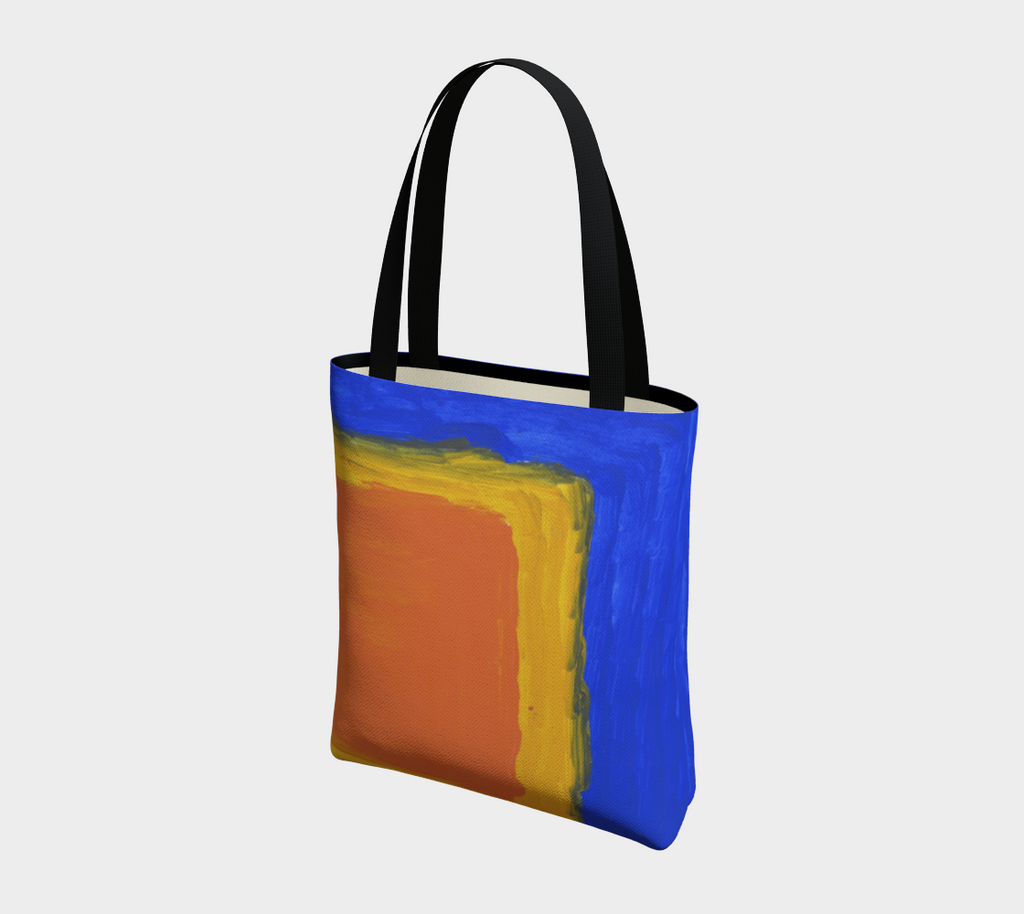 Tote bag with black double straps with blue background and large yellow and orange square in lower right hand corner