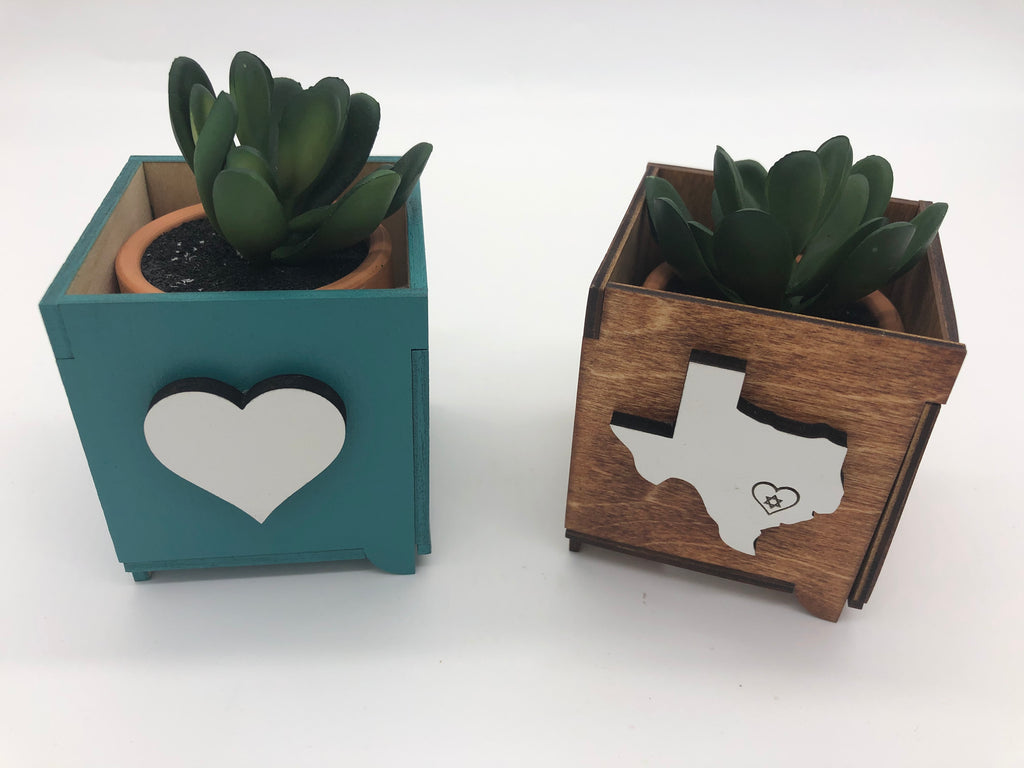 Two square wooden planters with small succulent plants in them.  The left planter is a light blue with a white heart.  The right planter is wood with a white Texas with a heart and Jewish star graphic over Houston
