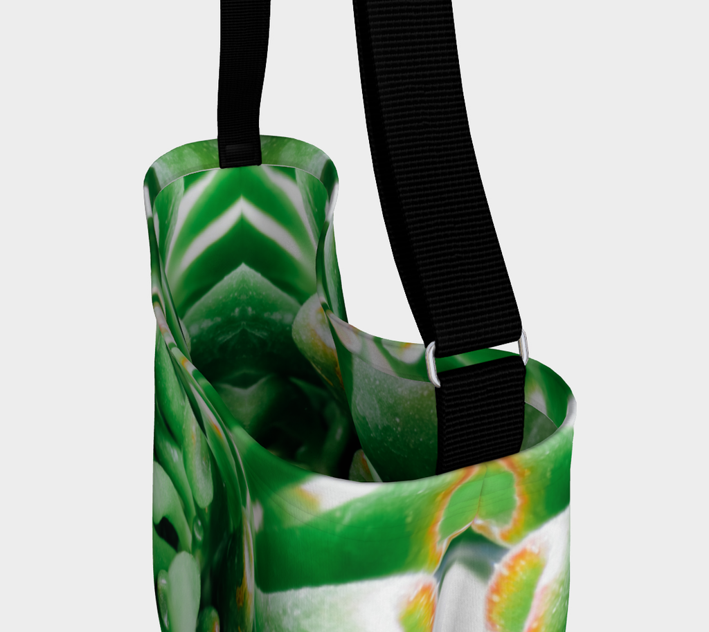 Close up view of Crossbody totebag with single black strap depicting close up view of green succulent plant