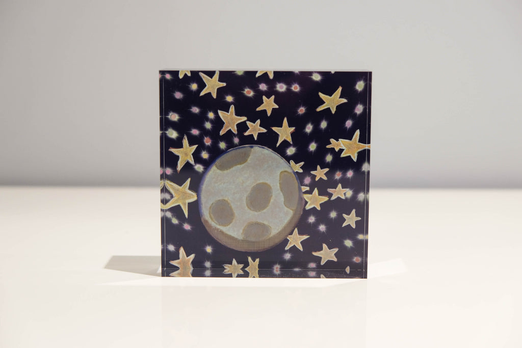 Front view of Acrylic block depicting outer space with a blue background and golden stars with Earth in the center