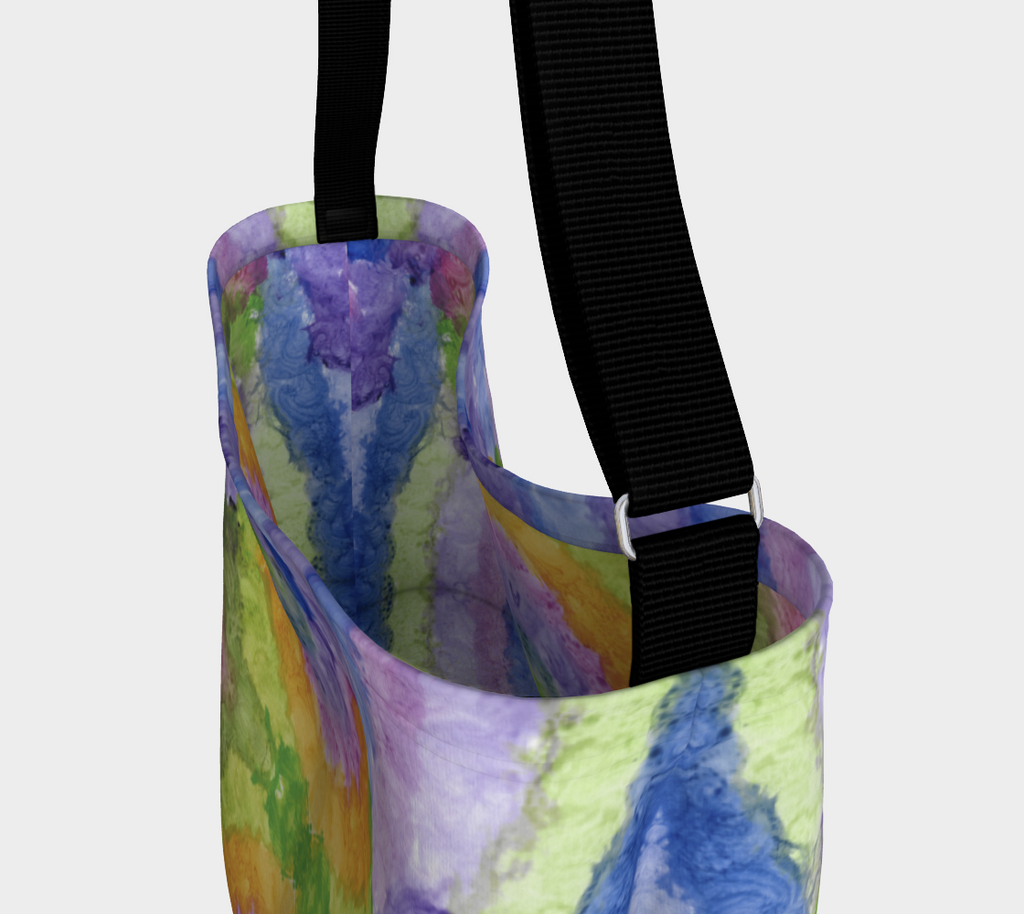 Close up view of Crossbody bag with black strap with fluffy blue, lavender, orange and green swirls