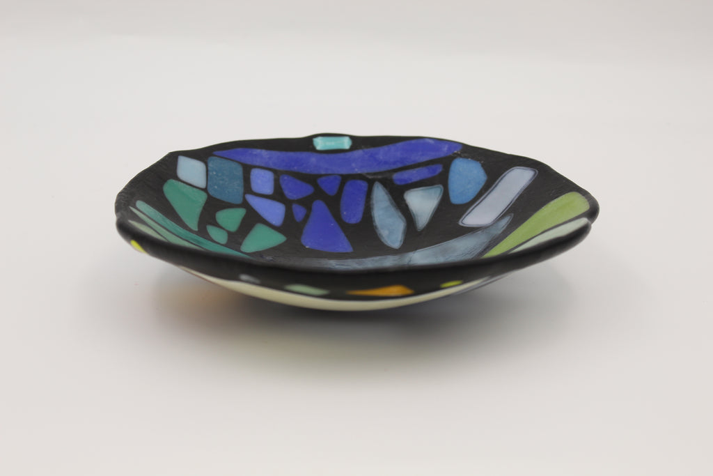 Black glass fused bowl with green, teal, and indigo abstract shapes