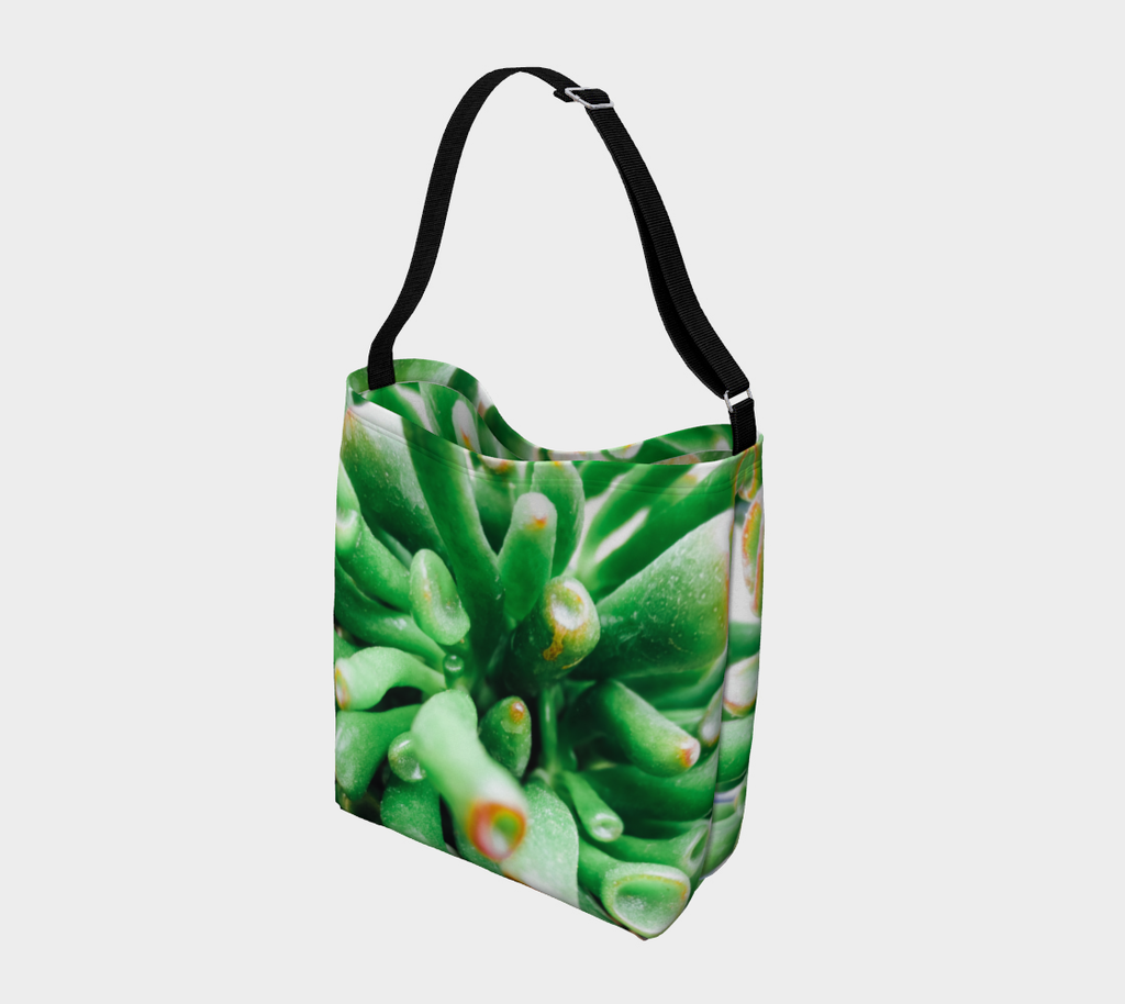 Crossbody totebag with single black strap depicting close up view of green succulent plant