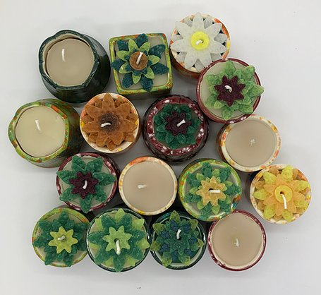 Pottery votives with hand poured candles, some of which are flower shapes