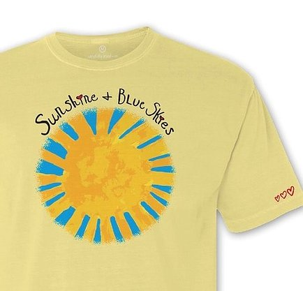 Close up view of yellow t shirt with golden sun with blue rays beneath Sunshine and Blue Skies slogan