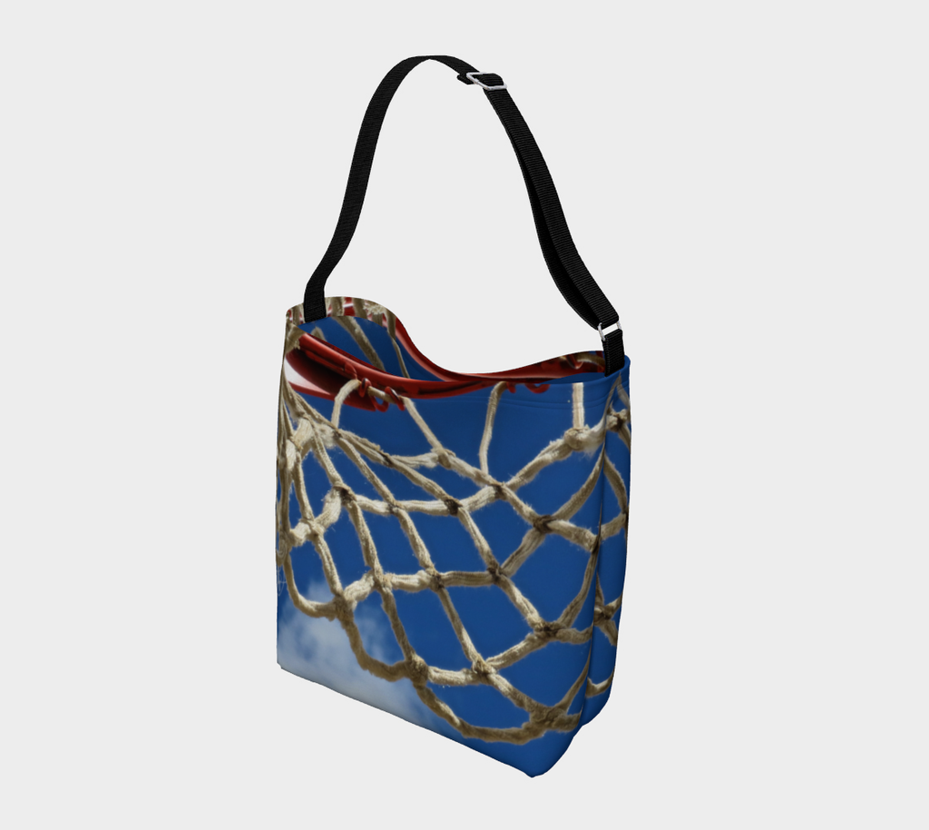 Crossbody totebag with single black strap with blue background and close up view of white basketball netting and red basketball rim