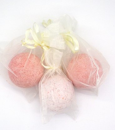 Two dark pink and one light pink bath bomb in cellophane packaging with yellow ribbons