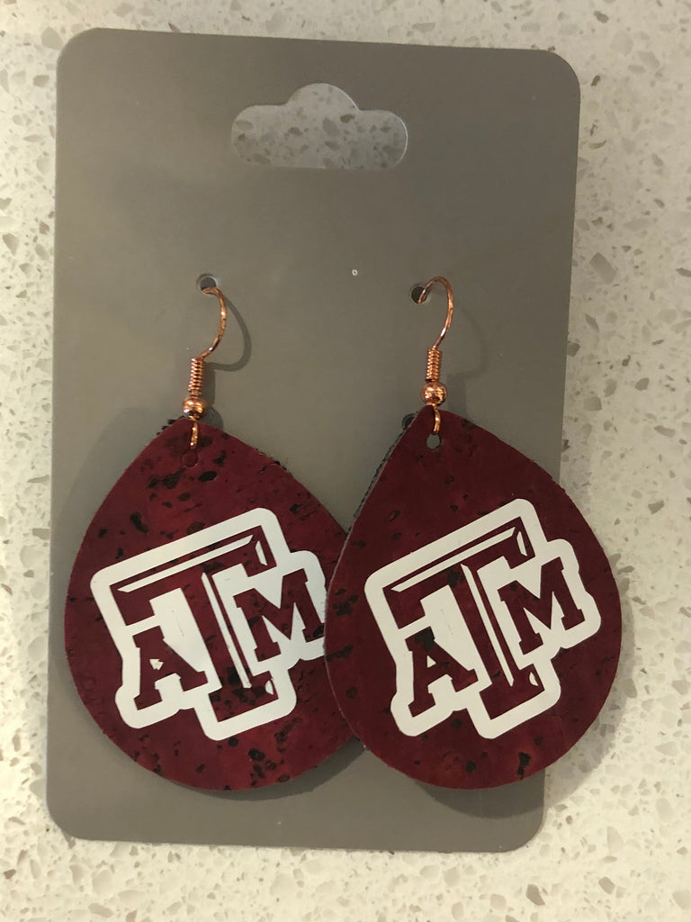 Tear drop shaped maroon leather earrings with A&M logo