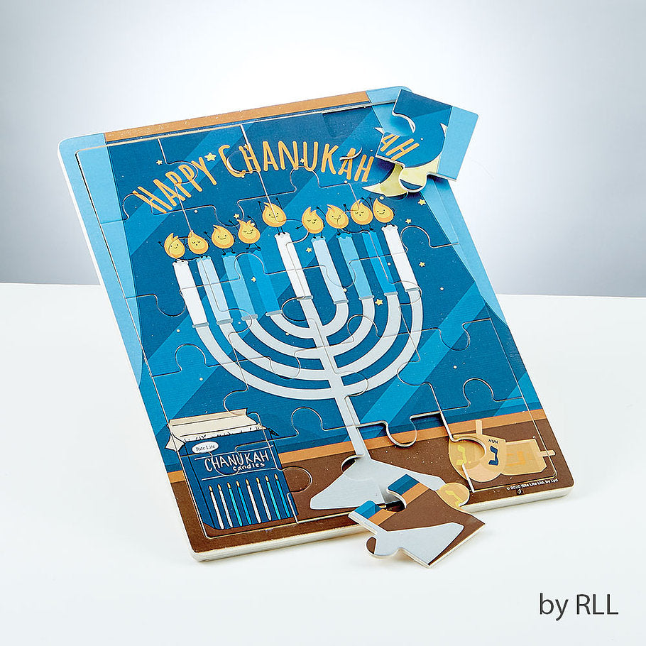 Happy Chanukah wooden puzzle with picture of white menorah, wooden dreidels and blue box of Chanukah candles