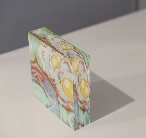 Tilted view of Acrylic block depicting 2 eggs sunny side up with side of bacon and a silver fork