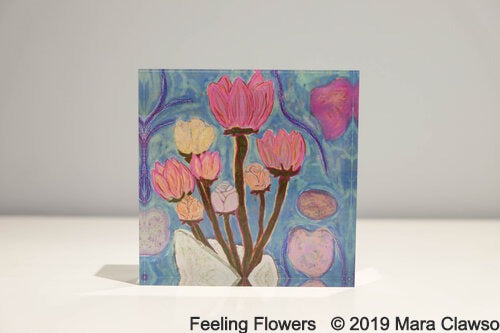Acrylic block with light blue background and bouquet of pink, yellow, and light orange flowers with brown stems
